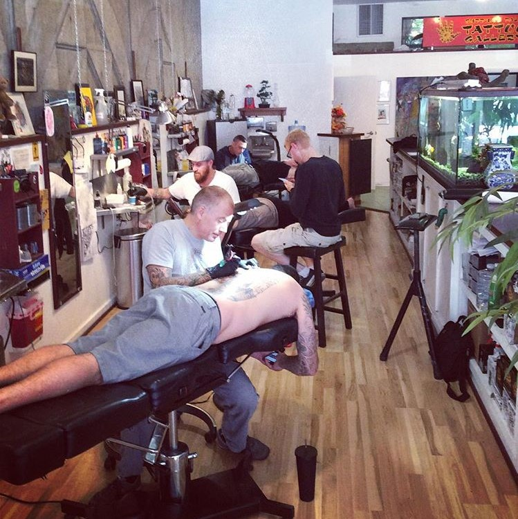 Christian Nolan, Vince Garcia and Clint Hillman all tattooing different people in the shop